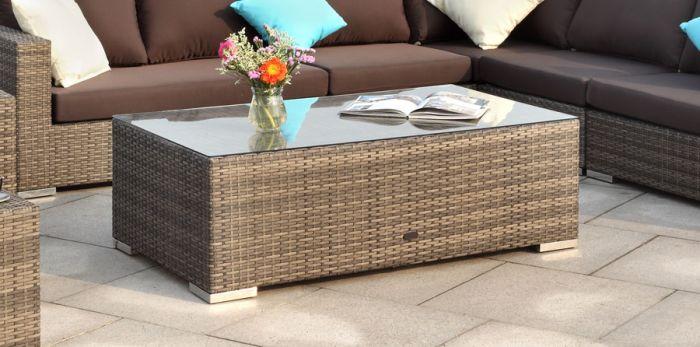 Stort rektangulært rotting bord med glassplate på en uteplass med blomster og et magasin. Puter i tilhørende utendørs sofagruppe. Sommer på terrassen | SparMax