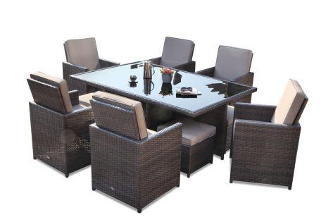 Flott spisebord med glassbord og seks stoler i rotting med fine brune puter. Hagemøblene er brunmix farge og det står blomster på bordet. SparMax